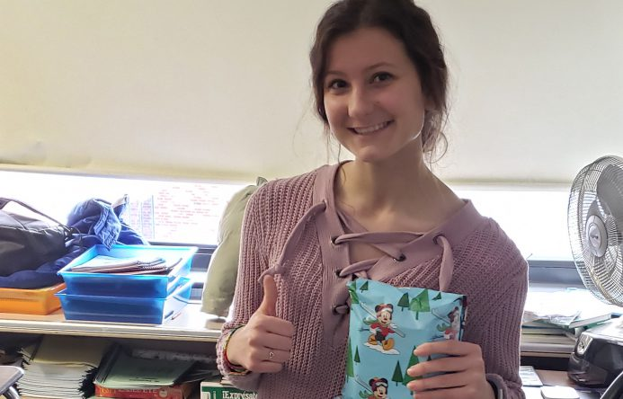 This is an image of a student holding a gift