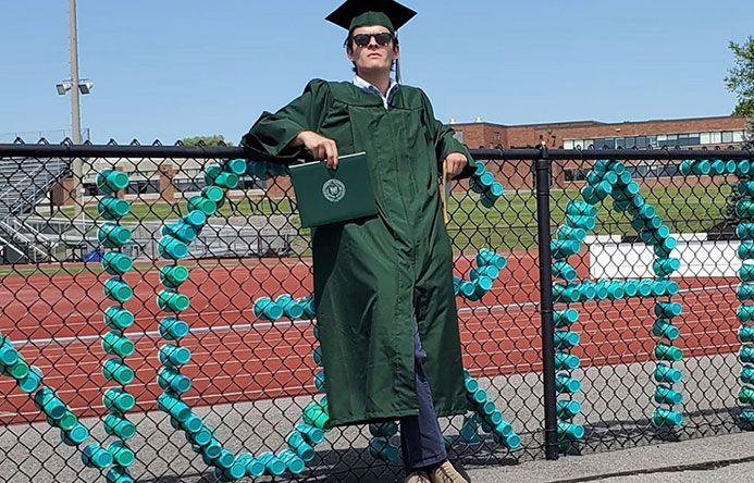 This is an image of a graduate standing next to a fence