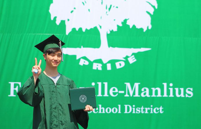 This is an image of a graduate making the peace sign