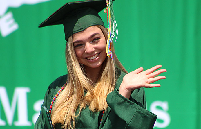 This is an image of a graduate waving