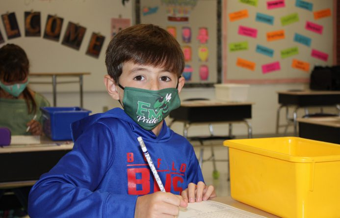 Boy wearing F-M Pride face mask looking at the camera.
