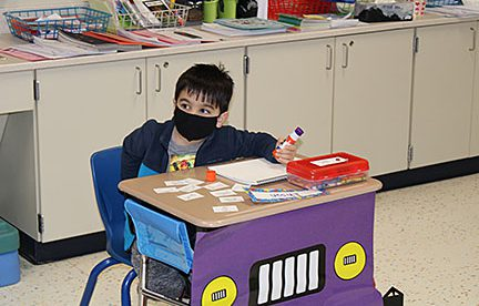 Elementary student seated at classroom desk.