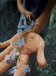 Close up of a hand holding blue flowers.