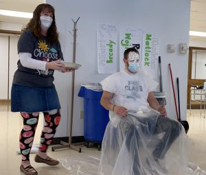 Person standing holding a pie next to a person seated with whipped cream on their face.