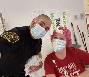 Two people wearinig face masks with traces of whipped cream on their faces lean together.