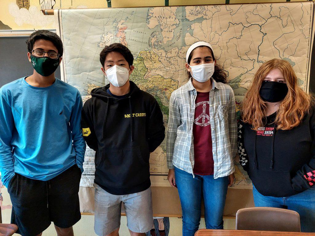 Four students standing shoulder-to-shoulder.