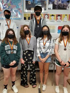 Students standing side-by-side in a group wearing face masks.