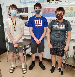 Three students standing side-by-side wearing face masks.