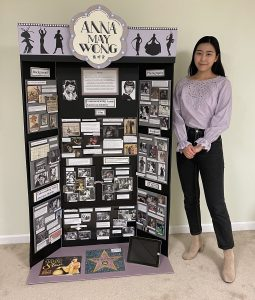 Student standing next to poster display.