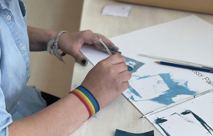 Student painting individual mural squares.
