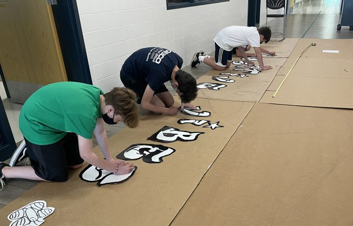 Students tracing mural design on cardboard.