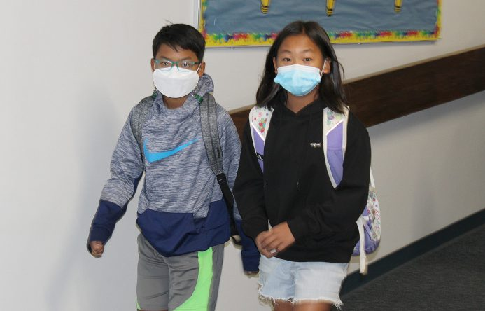 Two students walking in school hallway.